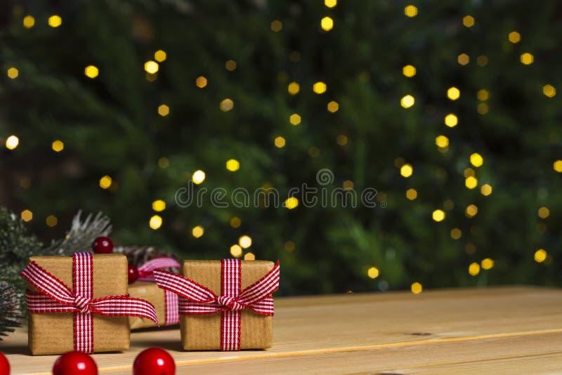 Kerstmisgiften op lijst, de achtergrond van de Kerstmisboom stock afbeeldingen