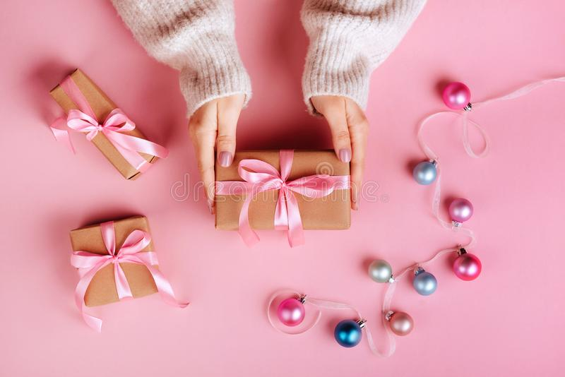 Kerstmisgrens met giftvakjes, ballen, decoratie en lovertjes op de roze mening van de lijstbovenkant royalty-vrije stock afbeelding