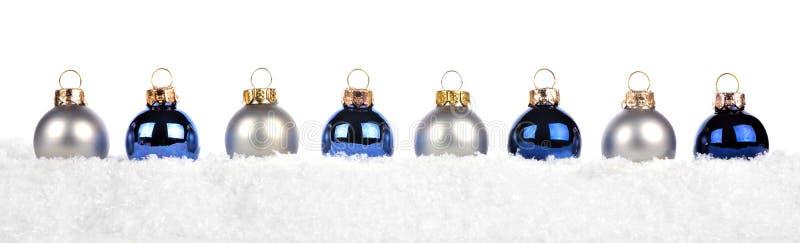 Kerstmisgrens van blauwe en zilveren die ornamenten in sneeuw op wit wordt geïsoleerd stock fotografie