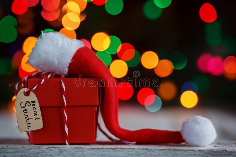 Kerstmisheden of doos voor geheime santa met Kerstmanhoed De kaart van de groet stock fotografie