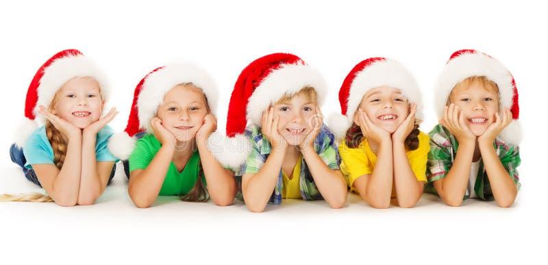 Kerstmisjonge geitjes die in rode hoed glimlachen royalty-vrije stock afbeelding