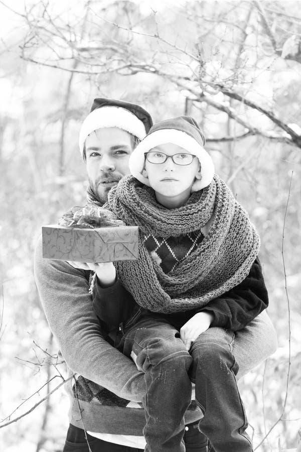 Kerstmisjongen en mensenvader met heden in de winter openlucht royalty-vrije stock afbeelding