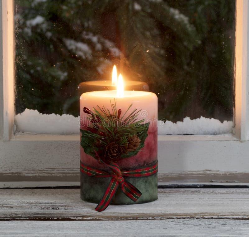 Kerstmiskaars die op venstervensterbank gloeien met sneeuw altijdgroene bustehouder stock afbeelding