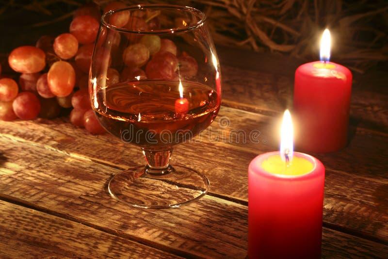 Kerstmiskaarsen, druiven en glas met cognac of wisky op houten achtergrond De decoratie van Kerstmis stock afbeelding