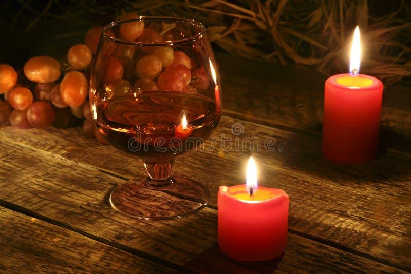 Kerstmiskaarsen, druiven en glas met cognac of wisky op houten achtergrond De decoratie van Kerstmis royalty-vrije stock foto's