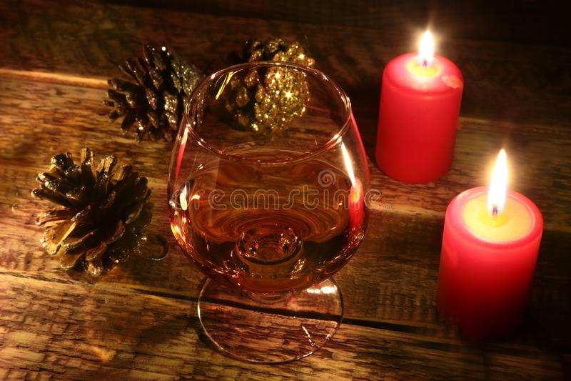 Kerstmiskaarsen en glas met cognac of wisky op houten achtergrond De decoratie van Kerstmis stock fotografie