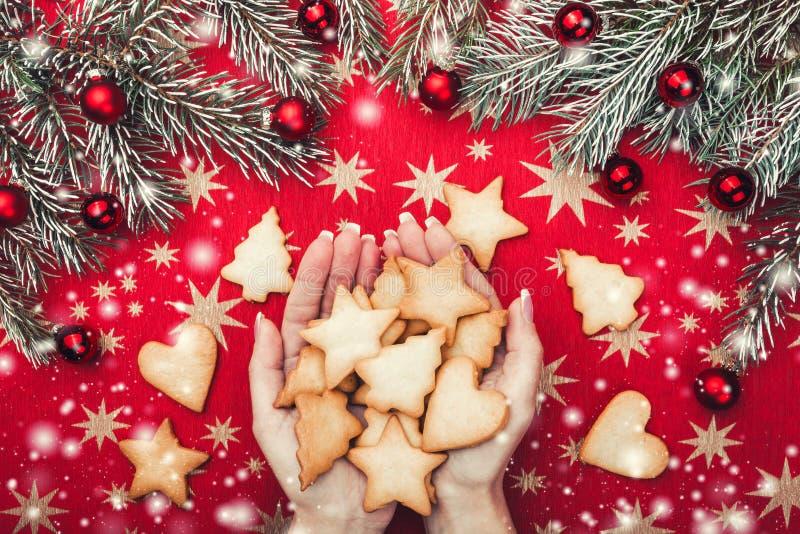 Kerstmiskaart, dames` handen die Kerstmiskoekjes houden Spartakken met rode ballen Hoogste mening Sneeuweffect stock foto
