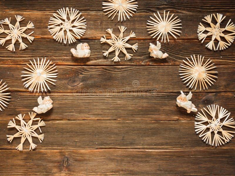Kerstmiskader met strosneeuwvlokken en engelen op een donkere woode stock foto's