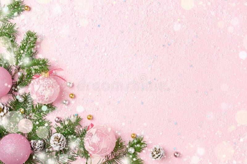 Kerstmiskader van Nieuwjaarornamenten en sneeuw op roze backgroun stock afbeeldingen