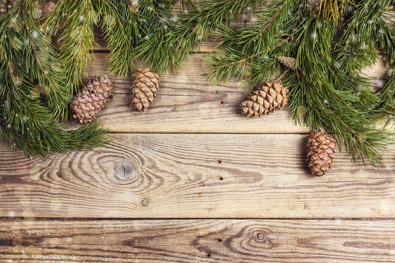 Kerstmiskader van pijnboomtakken en cederkegels wordt gemaakt op plattelander die royalty-vrije stock foto