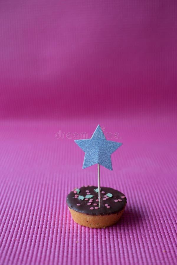 Kerstmiskoekje met ster decoratieve topper op roze achtergrond stock foto