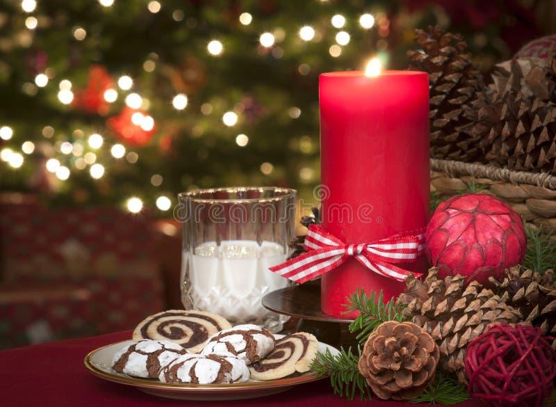 Kerstmiskoekjes en Melk die op Santa Claus in Kaarslicht wachten met een Aangestoken Kerstboom op achtergrond op Kerstavond stock foto's