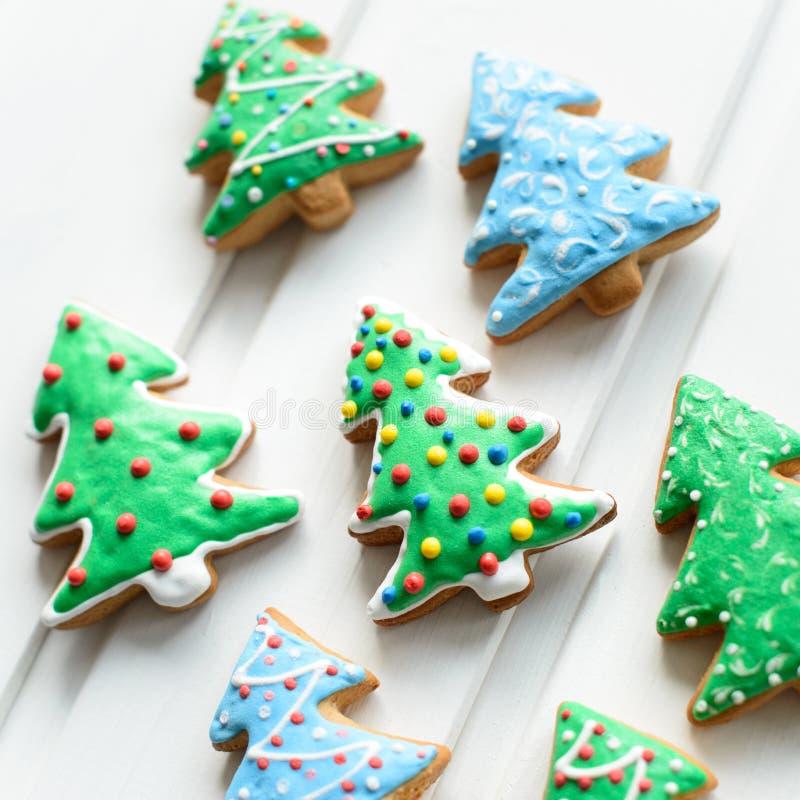 Kerstmiskoekjes in vorm van spar met feestelijke decoratie op witte houten achtergrond Nieuw jaar en Kerstmisconcept stock afbeelding