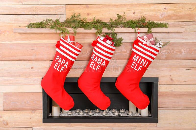 Kerstmiskousen die op houten muur dichtbij decoratieve open haard hangen stock afbeelding