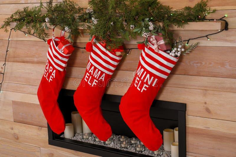 Kerstmiskousen die op houten muur dichtbij decoratieve open haard hangen stock afbeeldingen