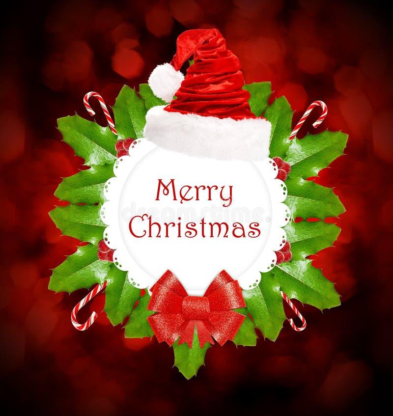 Kerstmiskroon met hulst, snoepjes, santahoed en rode boog royalty-vrije stock fotografie
