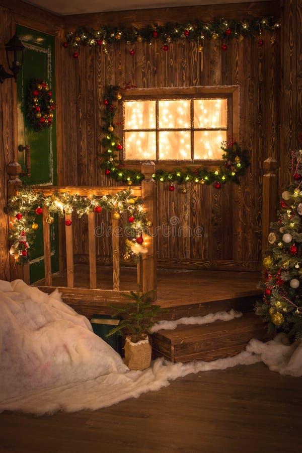 Kerstmiskroon op groene deur, venster verfraaide houten bac van w stock afbeelding
