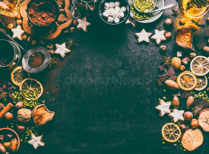 Kerstmiskruiden, chocolade en koekjesachtergrond met ingrediënten voor baksel en zoet voedsel: noten, droge vruchten, chocolade stock afbeelding