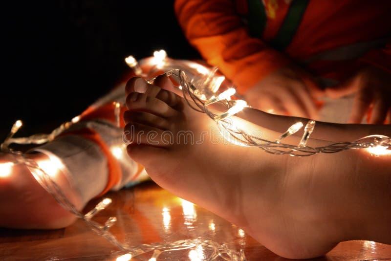 Kerstmislichten met kindvoeten stock afbeelding