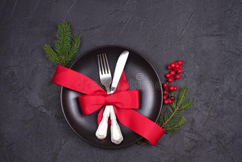 Kerstmislijst die met plaat, bestek, rode lint en bessen plaatsen De wintervakantie en feestelijke achtergrond stock foto