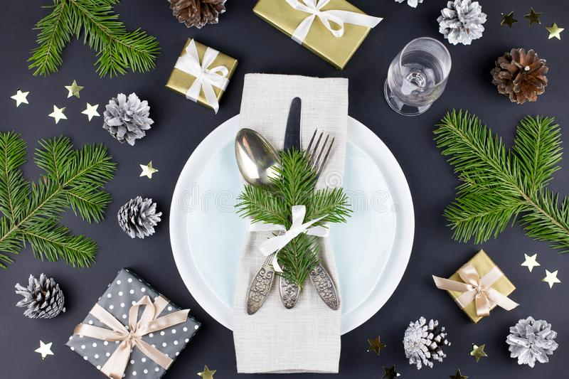 Kerstmislijst die met platen, tafelzilver, giftvakje en decoratie in zwarte en gouden kleuren plaatsen royalty-vrije stock foto