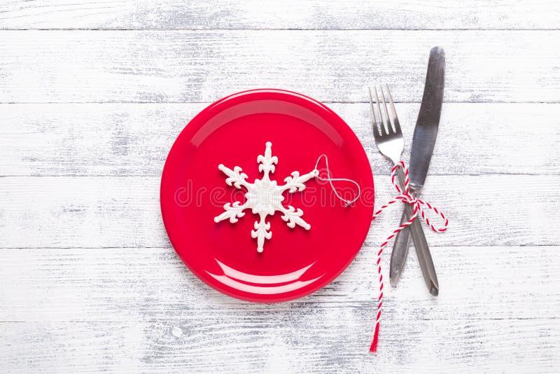 Kerstmislijst die met rode plaat, tafelzilver op lichte houten achtergrond plaatsen stock afbeelding