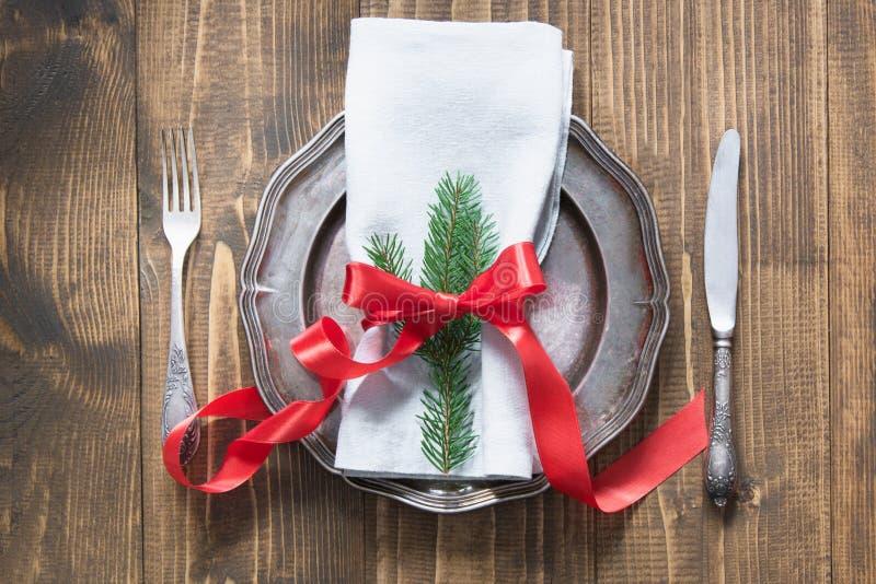 Kerstmislijst die met suikergoedriet en rood lint als decor, wijnoogst plaatsen dishware, tafelzilver en decoratie op houten raad royalty-vrije stock foto
