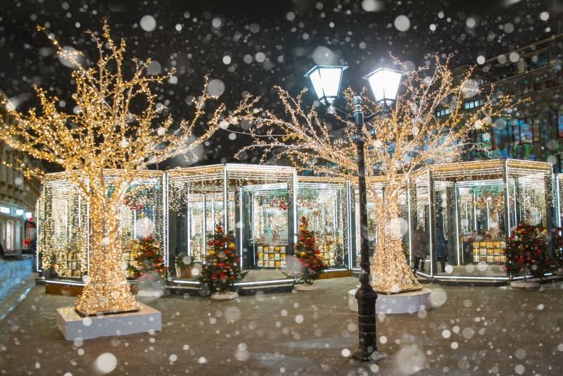 Kerstmismarkt, elektrische lantaarn, de boom van decoratiekerstmis in de nacht met getrokken sneeuw royalty-vrije stock foto
