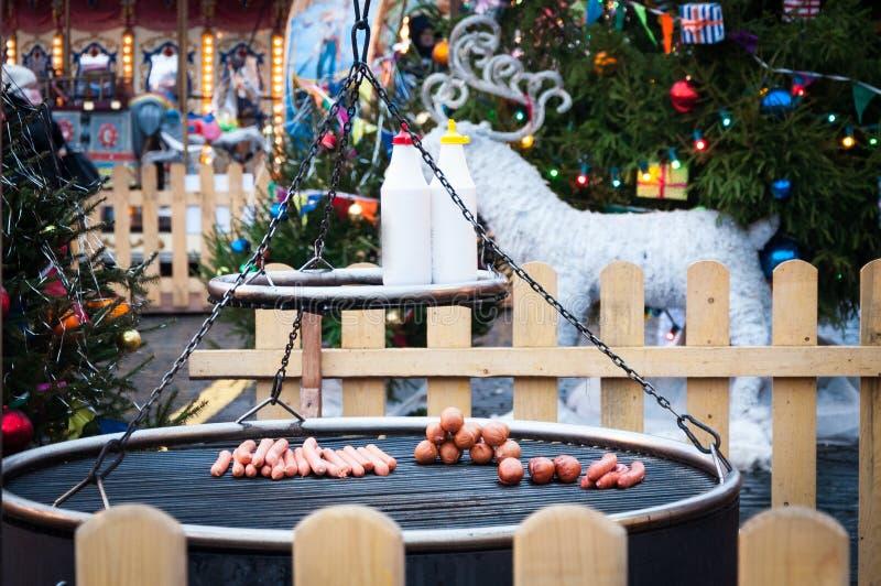 Kerstmismarkt in Rood Vierkant, Moskou Voorbereiding van worsten en worsten op een grill voor hotdogs royalty-vrije stock fotografie