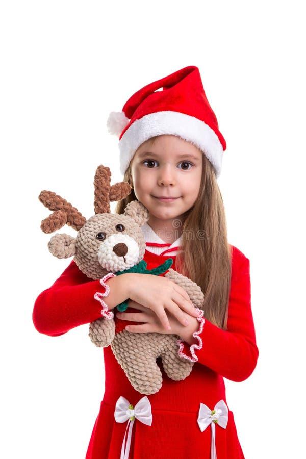 Kerstmismeisje die het herten zachte stuk speelgoed koesteren, die een santahoed dragen over een witte achtergrond wordt geïsolee stock foto