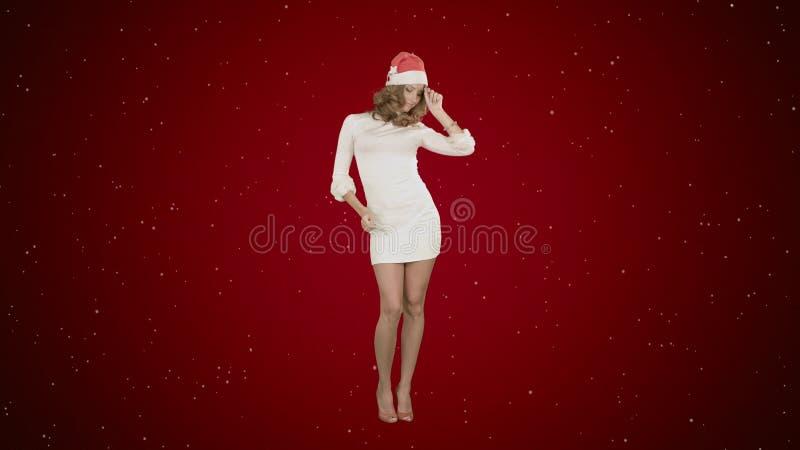 Kerstmismeisje in santahoed het dansen het gelukkige lachen hebbend pret op rode achtergrond met sneeuw royalty-vrije stock afbeelding
