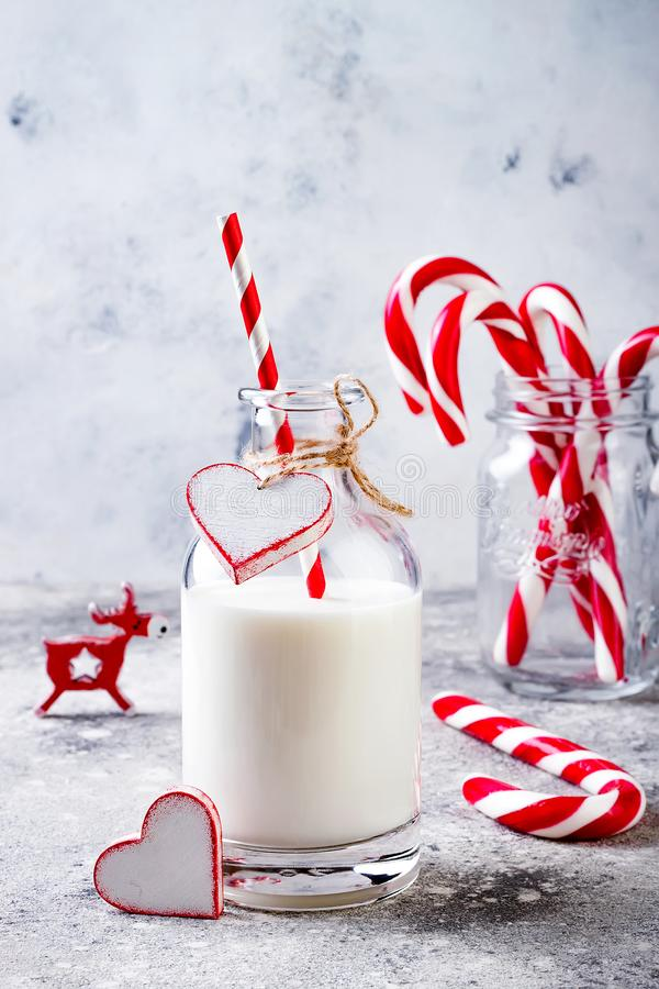 Kerstmismelk voor Kerstman in fles met stro en pepermuntsuikergoedriet De partijdrank van de Kerstmisvakantie stock fotografie