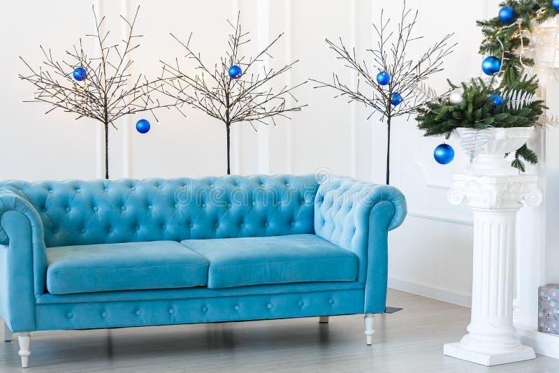 Kerstmisochtend, exemplaarruimte Klassieke flats met blauwe dichtgeknoopte bank, verfraaide spar stock afbeelding