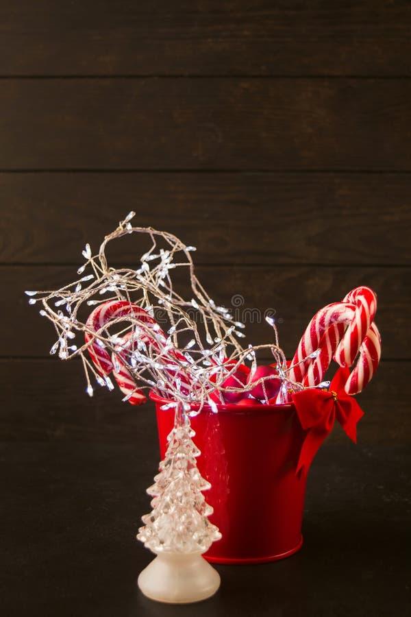 Kerstmisornament van de glasspar en rode emmer met slinger, suikergoedriet en boog stock afbeelding
