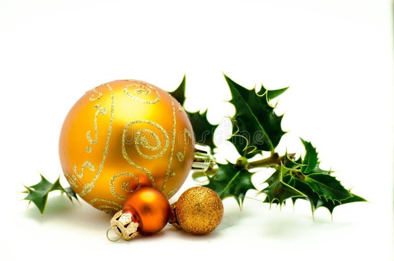 Kerstmisornamenten - oranje bal met groene hulst stock fotografie