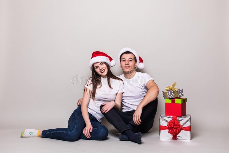 Kerstmispaar met giften het zitten stock fotografie