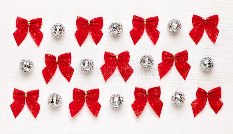Kerstmispatroon van rode bogen en spiegelballen op witte houten achtergrond royalty-vrije stock foto