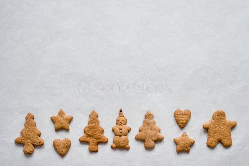 Kerstmispeperkoek in de samenstelling van sneeuwman, Kerstboom die, hart, ster, op een witte achtergrond liggen stock afbeeldingen