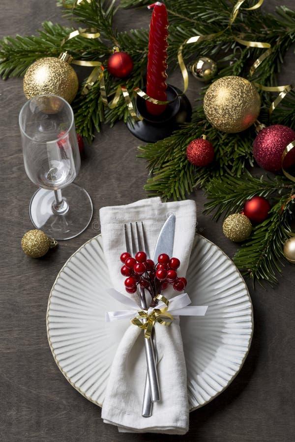 Kerstmisplaats die met vork en messen, glas, lint en Kerstmisdecoratie plaatsen stock afbeelding