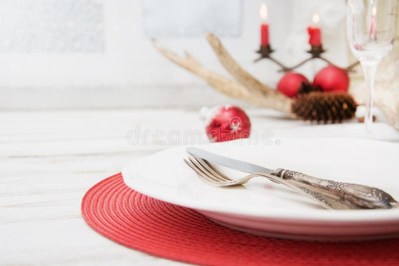 Kerstmisplaats die met witte dishware, bestek, tafelzilver en rode decoratie op houten raad plaatsen Kerstmis royalty-vrije stock afbeelding