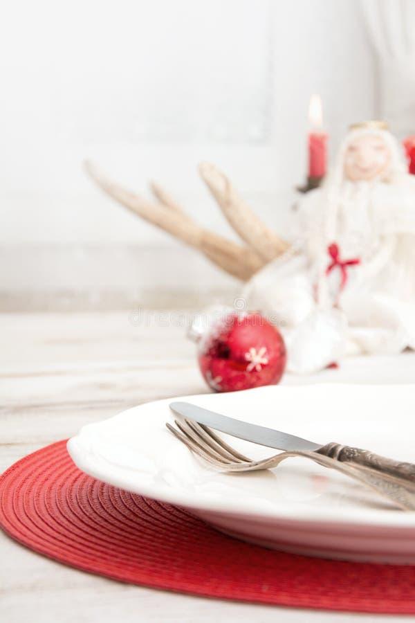 Kerstmisplaats die met witte dishware, bestek, tafelzilver en rode decoratie op houten raad plaatsen Kerstmis royalty-vrije stock foto's