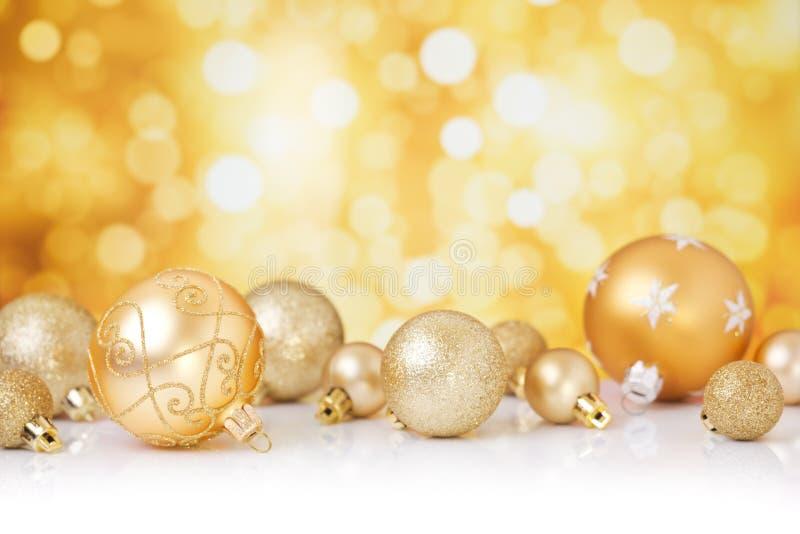 Kerstmisscène met gouden snuisterijen, gouden achtergrond stock fotografie