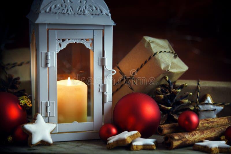 Kerstmisscène met lantaarn en een brandende kaars, giften in kraf stock foto