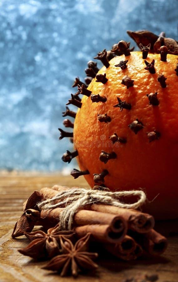 Kerstmissinaasappelen De sinaasappelen met kruidnagel en cinamon stokkenclose-up tegen bevroren venster defocused royalty-vrije stock foto