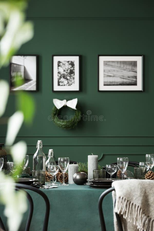 Kerstmisslinger en zwart-witte affiches op groene muur van eetkamerreeks voor Kerstmisdiner stock afbeeldingen