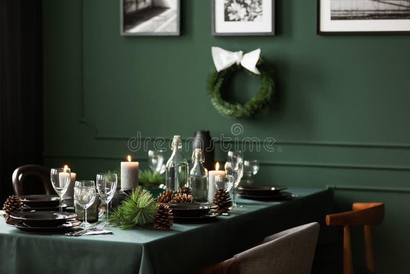Kerstmisslinger en zwart-witte affiches op groene muur van eetkamerreeks voor Kerstmisdiner royalty-vrije stock afbeeldingen