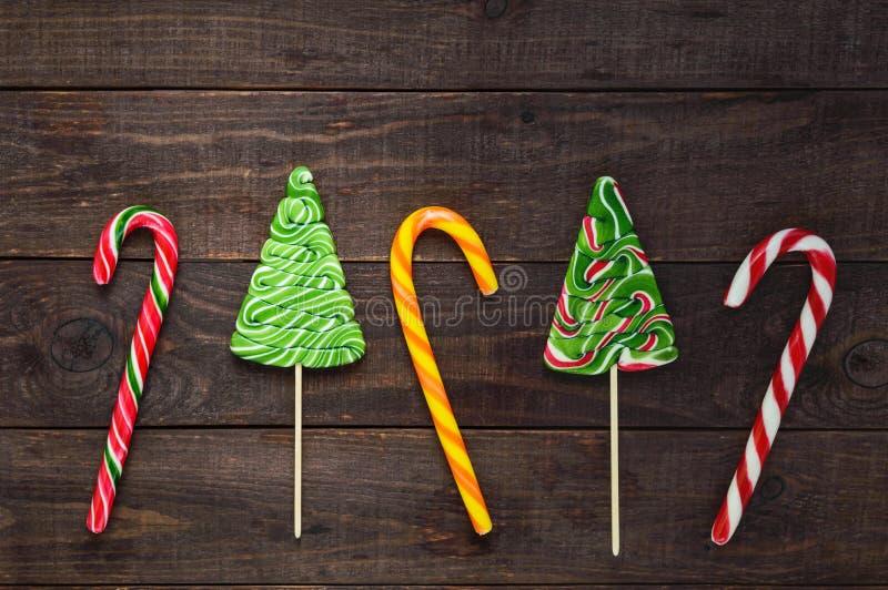 Kerstmissnoepjes: helder gekleurd suikergoed in de vorm van een riet en een spar op een donkere houten achtergrond Feest achtergr royalty-vrije stock afbeelding