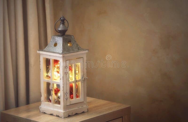 Kerstmissnuisterijen en gouden feelichten in lantaarn stock afbeelding