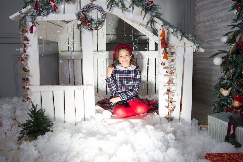 Kerstmissprookje Het kleine leuke meisje viert Kerstmis Het jong geitjemeisje zit houten stuk speelgoed huisachtergrond Kind royalty-vrije stock afbeeldingen