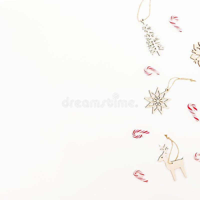 Kerstmisstilleven met houten boomdecoratie, sneeuwvlokken en suikergoedriet op witte achtergrond Vlak leg, hoogste mening Het nie stock afbeelding